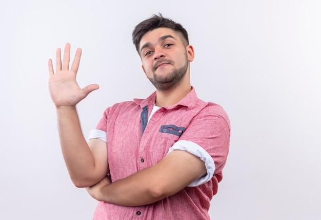 Jovem rapaz bonito vestindo uma camisa pólo rosa sorrindo e mostrando cinco com os dedos em pé sobre uma parede branca Foto gratuita