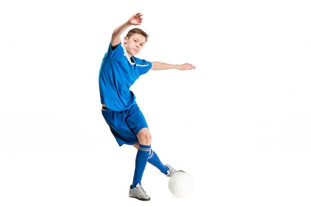 Jovem rapaz com bola de futebol, fazendo o chute voador Foto gratuita