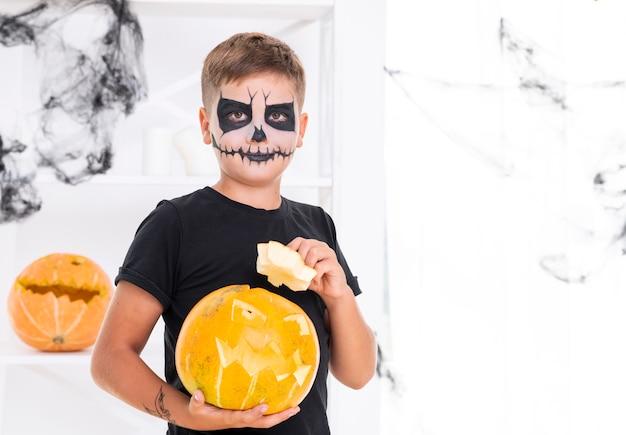 Jovem rapaz com rosto pintado segurando uma abóbora Foto gratuita