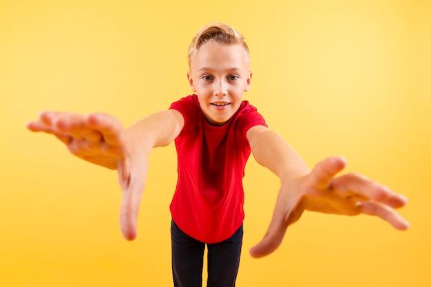 Jovem rapaz de ângulo baixo preparado para pegar com as mãos Foto gratuita