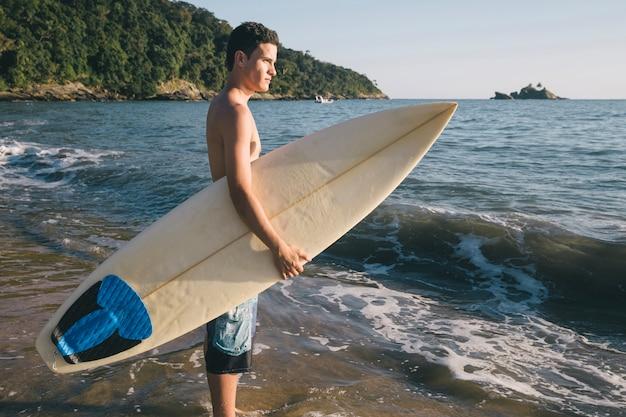 Jovem rapaz em um dia de surf Foto gratuita