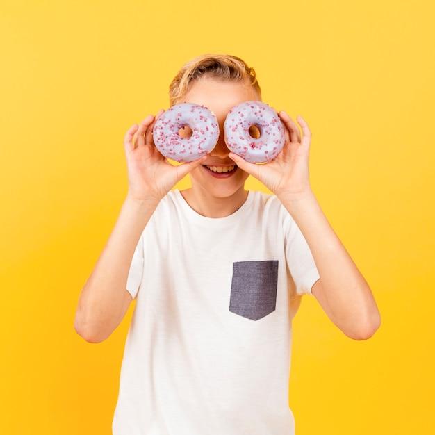 Jovem rapaz fazendo óculos com donuts Foto gratuita