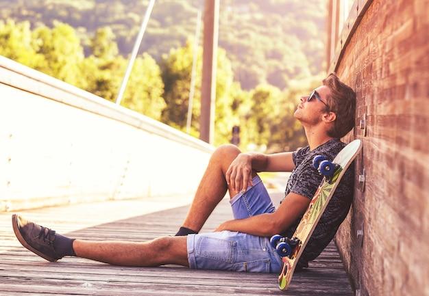 Jovem rapaz sentado em uma ponte de madeira com seu skate. Foto Premium