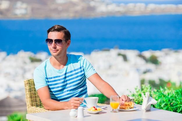 Jovem rapaz tomando café da manhã no café ao ar livre com uma vista incrível na cidade de mykonos. homem bebendo café quente no terraço do hotel de luxo com vista para o mar no restaurante do resort. Foto Premium