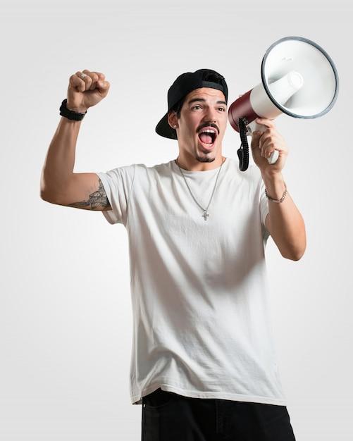 Jovem rapper homem animado e eufórico, gritando com um megafone, sinal de revolução e mudança, incentivando outras pessoas a mover-se, líder personalidade Foto Premium