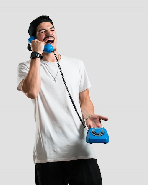 Jovem rapper homem rindo alto, se divertindo com a conversa, chamando um amigo ou um cliente Foto Premium