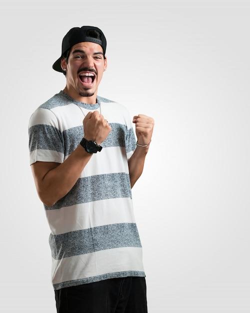 Jovem rapper muito feliz e animado, levantando os braços, comemorando uma vitória ou sucesso, ganhando na loteria Foto Premium