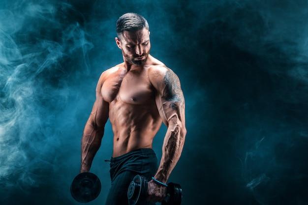 Jovem rasgou o fisiculturista de homem com abs perfeito, ombros, bíceps, tríceps e peito, posando com um haltere Foto Premium