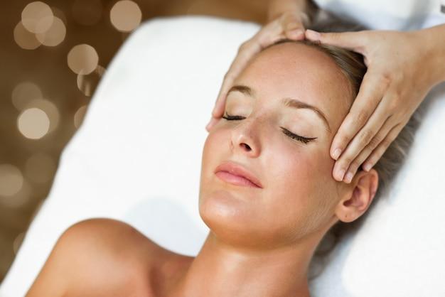 Jovem recebendo uma massagem na cabeça em um centro de spa. Foto gratuita