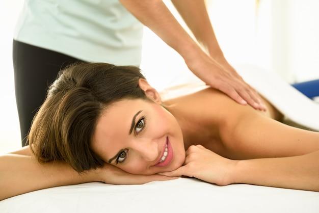 Jovem recebendo uma massagem nas costas em um centro de spa. Foto gratuita