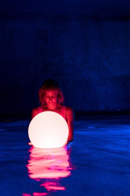Jovem relaxada na piscina com luz neon Foto Premium