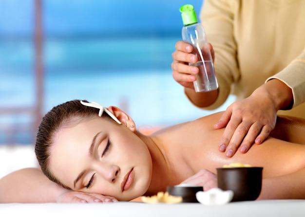 Jovem relaxante linda mulher recebendo massagem com óleo cosmético em salão de spa Foto gratuita