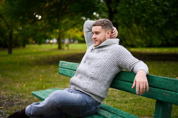 Jovem relaxante no banco no parque Foto gratuita