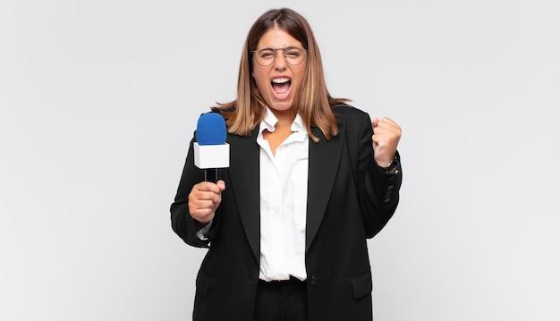 Jovem repórter gritando agressivamente com uma expressão de raiva ou com os punhos cerrados celebrando o sucesso Foto Premium
