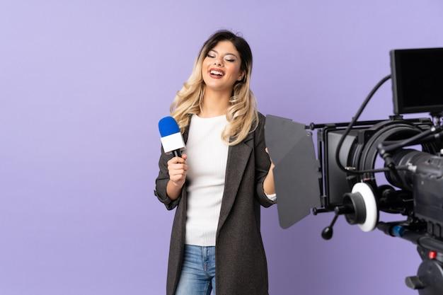 Jovem repórter segurando um microfone e reportando notícias isoladas na parede roxa com polegares para cima gesto e sorrindo Foto Premium
