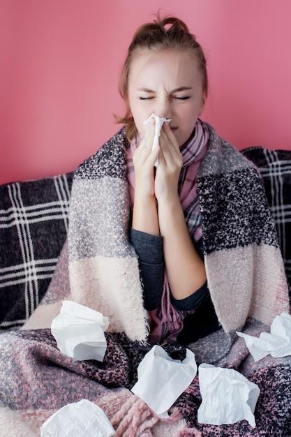 Jovem retrato horizontal com um lenço e corrimento nasal no perfil, espirrando de gripe, modelo feminino de pele branca na parede rosa. conceito de saúde e médico. Foto Premium