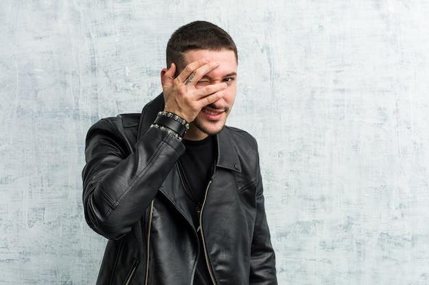 Jovem roqueiro piscar para a câmera através dos dedos, rosto de vergonha de cobertura Foto Premium
