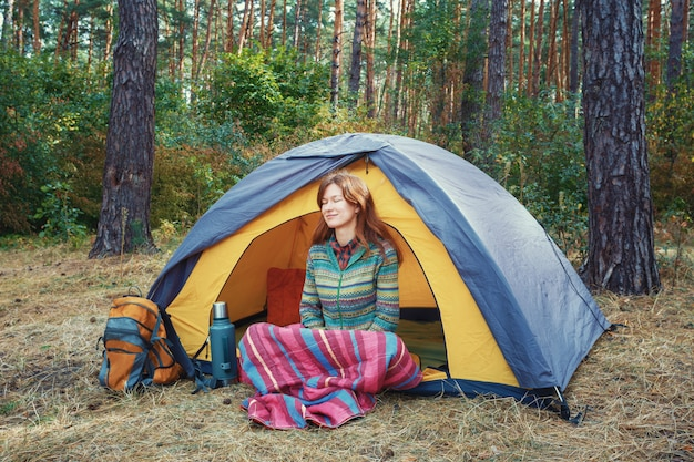 Jovem ruiva com olhos próximos, sentado na barraca cinza amarela, relaxante, curtindo a natureza na floresta de outono. Foto Premium
