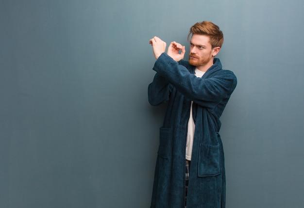 Jovem ruiva de pijama, fazendo o gesto de uma luneta Foto Premium