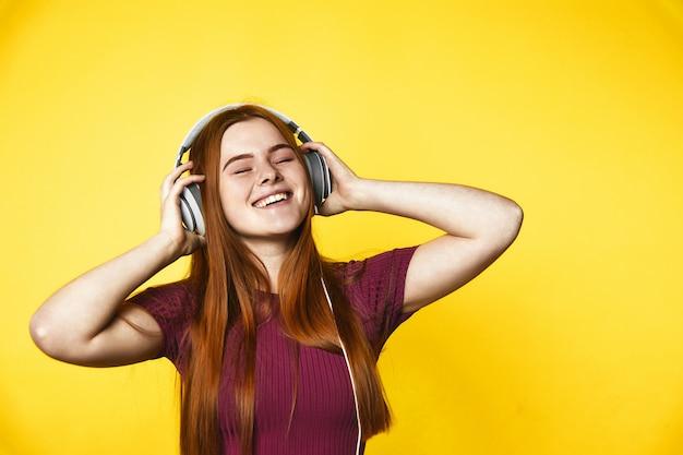 Jovem ruiva é feliz e ouvir música através de fones de ouvido com os olhos fechados Foto gratuita