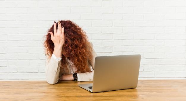 Jovem ruiva encaracolada mulher trabalhando com o laptop dela esquecendo algo Foto Premium