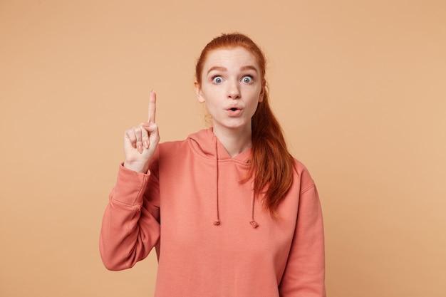 Jovem ruiva isolada em uma parede bege, apontando o dedo para cima e arregalando os olhos com uma ideia bem-sucedida Foto gratuita