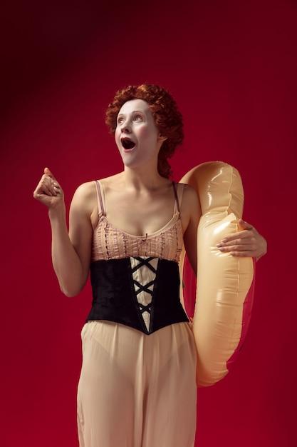 Jovem ruiva medieval como uma duquesa com espartilho preto e roupas de dormir em pé sobre o vermelho Foto gratuita