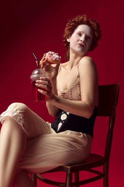 Jovem ruiva medieval como uma duquesa em espartilho preto e roupa de noite, sentada em uma cadeira na parede vermelha com uma bebida e donut. conceito de comparação de eras, modernidade e renascimento. Foto gratuita
