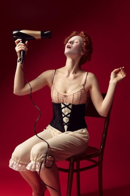 Jovem ruiva medieval como uma duquesa em espartilho preto e roupa de noite, sentada na cadeira na parede vermelha. arrumando o cabelo com secador. conceito de comparação de eras, modernidade e renascimento. Foto gratuita