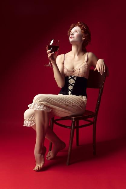 Jovem ruiva medieval como uma duquesa em espartilho preto e roupa de noite, sentada na cadeira na parede vermelha. beber vinho tinto. conceito de comparação de eras, modernidade e renascimento. Foto gratuita