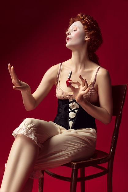 Jovem ruiva medieval como uma duquesa em espartilho preto e roupa de noite, sentada na cadeira na parede vermelha. usando esmalte de unha. conceito de comparação de eras, modernidade e renascimento. Foto gratuita