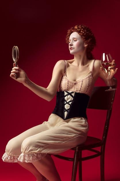 Jovem ruiva medieval como uma duquesa em espartilho preto e roupas de noite, sentada na parede vermelha com um espelho e um copo de vinho. conceito de comparação de eras, modernidade e renascimento. Foto gratuita