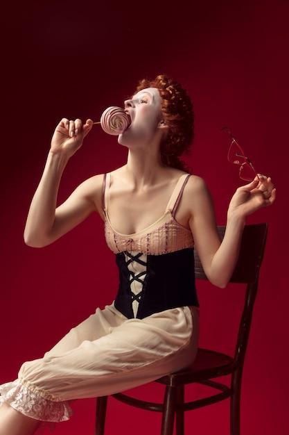 Jovem ruiva medieval como uma duquesa em espartilho preto, óculos escuros e roupa de noite, sentada em uma cadeira na parede vermelha com um doce. conceito de comparação de eras, modernidade e renascimento. Foto gratuita