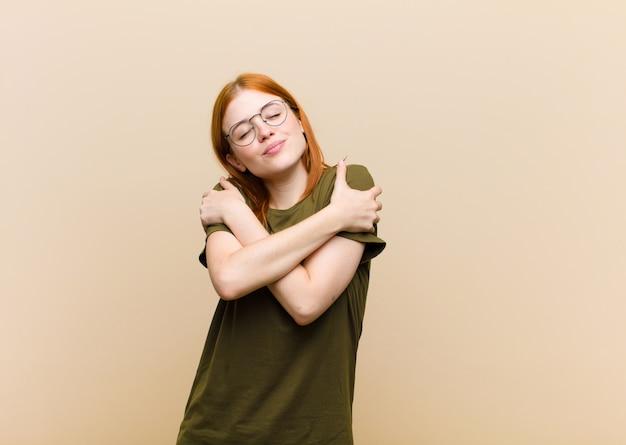 Jovem ruiva se sentindo apaixonada, sorrindo, abraçando e se abraçando, ficando solteira, sendo egoísta e egocêntrica Foto Premium