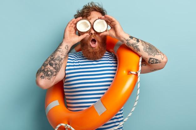 Jovem ruivo envergonhado com barba espessa, mantém olhos de coco nos olhos, olha para longe Foto gratuita