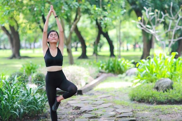 Jovem saudável e desportiva mulher fazer yoga alongamento ao ar livre Foto Premium