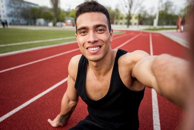 Jovem saudável fitness sentado na pista de corrida, tendo selfie no telemóvel Foto gratuita