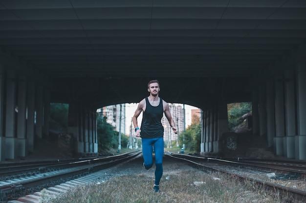 Jovem saudável, movimentando-se na cidade à noite. atleta masculino correndo sob a ponte ao longo dos caminhões da estrada de ferro. Foto Premium