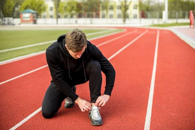 Jovem saudável, sentado na pista de corrida, amarrando o cadarço Foto gratuita