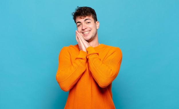 Jovem se apaixonando e parecendo fofo, adorável e feliz, sorrindo romanticamente com as mãos ao lado do rosto Foto Premium