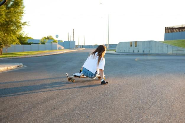 Jovem se divertindo com skate na estrada. jovem mulher patinando em um dia ensolarado Foto Premium