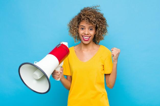Jovem se sentindo chocado, animado e feliz, rindo e comemorando o sucesso, dizendo uau! com um megafone Foto Premium
