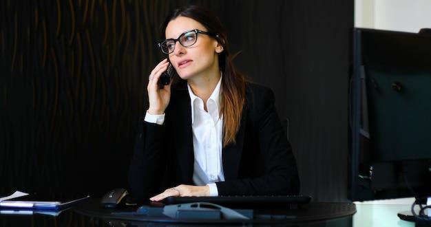 Jovem secretária ao telefone em seu escritório Foto Premium