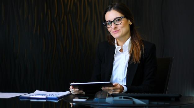 Jovem secretária pensativa usando um tablet digital na mesa dela sorrindo Foto Premium