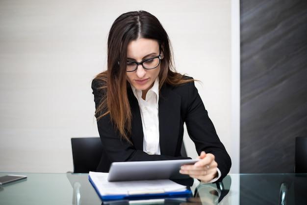 Jovem secretária pensativa usando um tablet digital na mesa dela Foto Premium