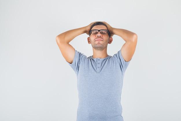 Jovem segurando a cabeça com as mãos em uma camiseta cinza, óculos e parecendo esperançoso Foto gratuita