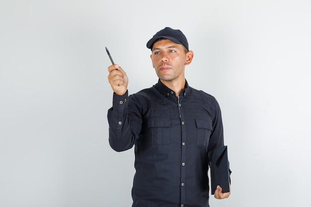 Jovem segurando caneta e pasta em uma camisa preta com tampa Foto gratuita