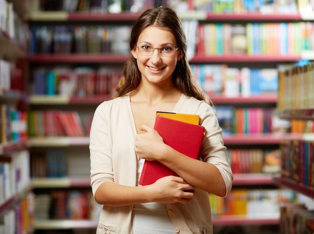 Jovem segurando livros em uma biblioteca Foto gratuita