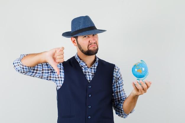 Jovem segurando o globo, mostrando o polegar para baixo na camisa, colete, chapéu e olhando descontente, vista frontal. Foto gratuita