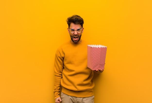 Jovem, segurando pipocas, gritando muito irritado e agressivo Foto Premium